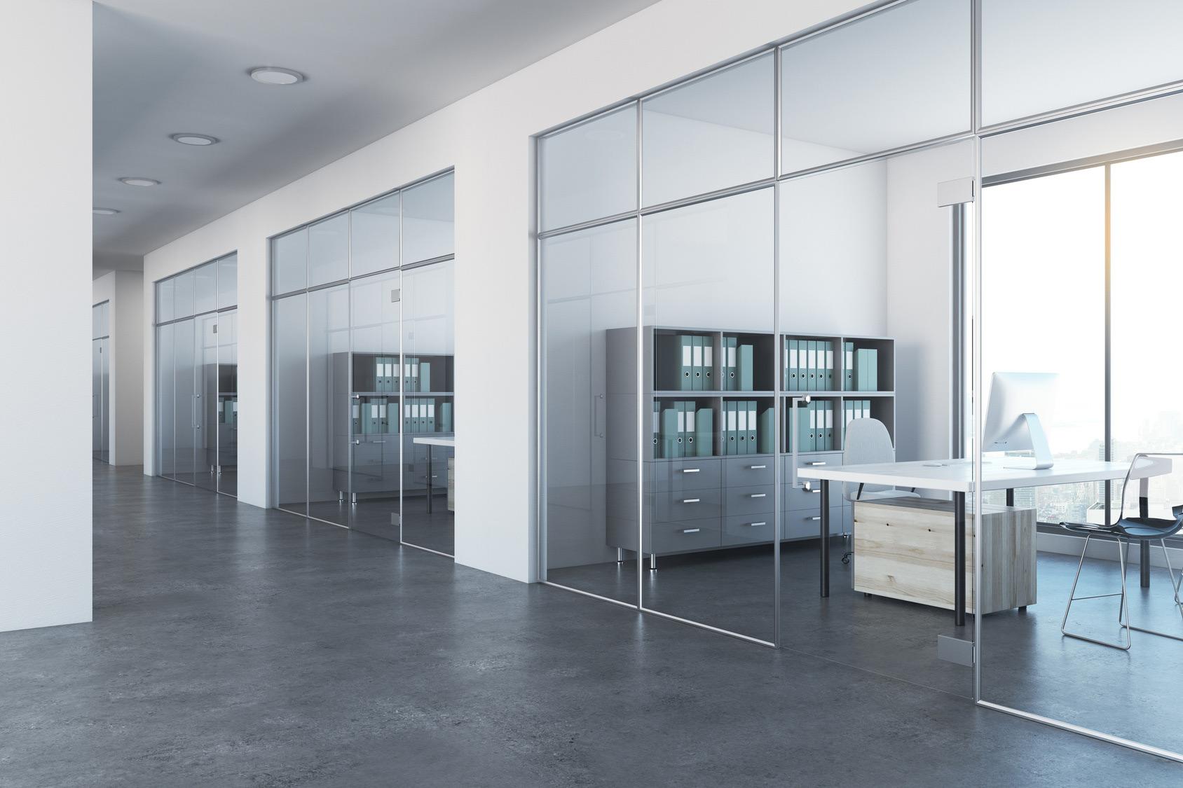 Biuro komórkowe, widok z korytarza na przestronne osobne gabinety umieszczone za przeszklonymi ścianami.